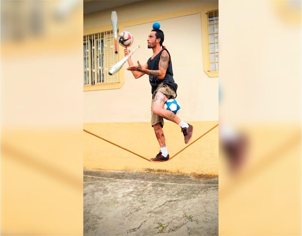 Vini Pirata na corda bamba com malabares no alto enquanto equilibra 3 bolas